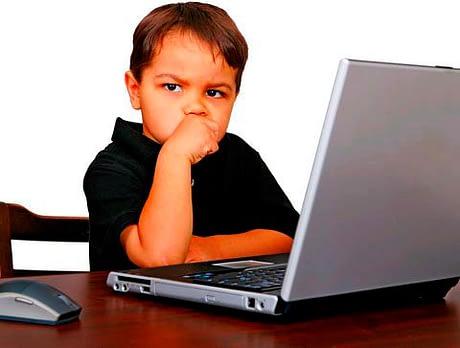 Мальчик в раздумьях за ноутбуком
